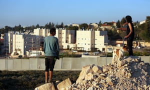 Palestinian boys, from the adjacent Jalazon refugee camp, look towards the Israeli settlement of Beit El, in the occupied West Bank north of Ramallah on April 7, 2015, as a new defensive wall is being installed around the settlement and next to a road used by Palestinians from the camp. AFP PHOTO/ABBAS MOMANIABBAS MOMANI/AFP/Getty Images
