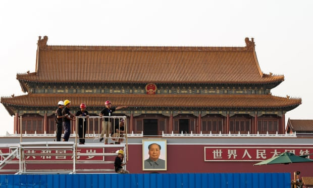 Workers assemble temporary seating in front of a giant portrait of Mao Zedong.