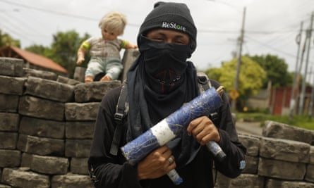 A young man poses with a handmade weapon, in front of a street barricade in Managua, Nicaragua, 15 June 2018.
