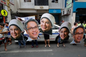 People parade cardboard cutouts of electoral hopefuls in the Philippines