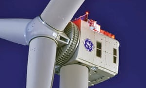 Close up of the head and boss of a giant wind turbine against a dark blue sky
