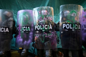 Police officers stand in line with defaced riot shields during a demonstration against police brutality in Bogota.