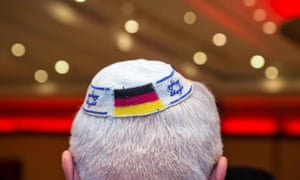 A man wearing a Jewish kippah skullcap with the flags of Germany and Israel.
