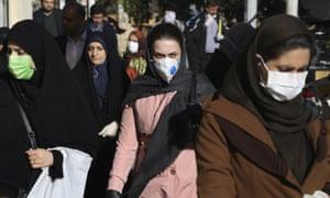 People wearing face masks walk on a sidewalk in downtown Tehran, Iran