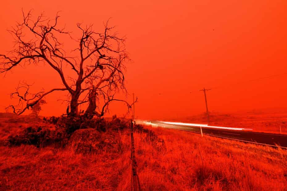 A long-exposure picture shows a car on a road as the sky turns red from the smoke of the Snowy valley bushfire on the outskirts of Cooma, New South Wales.