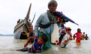 A Rohingya refugee pulls a child as they walk to the shore after crossing the Bangladesh-Myanmar border by boat on Sunday.