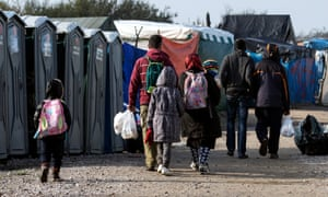 A family walks in the Calais camp