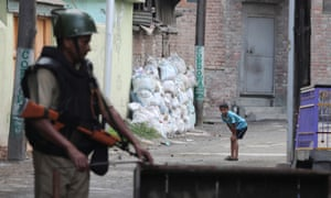 A Kashmiri child sees an Indian paramilitary soldier erecting a barricade in Srinagar.
