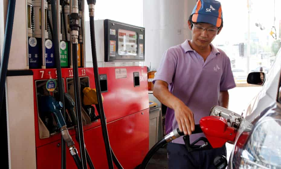 An attendant fills up a customer's car at an SK Energy Co. gas station in Seoul, South Korea