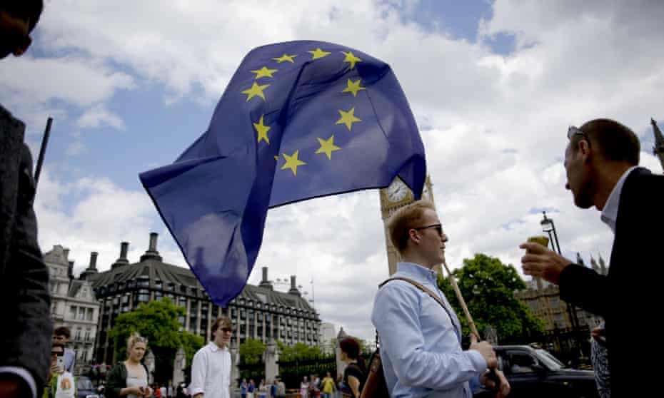 A remain supporter carries an EU flag outside parliament in London.
