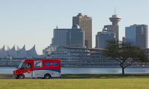 A postal truck drives by the Vancouver shore line in Canada.