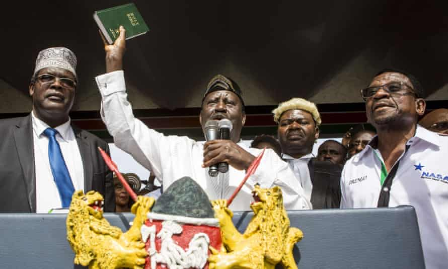 Kenya's opposition National Super Alliance leader, Raila Odinga, holds up a Bible as he swears himself in as the 'people's president'.