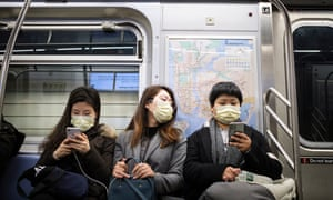 People wear masks to cover their faces while riding the subway in New York on 31 January 2020.