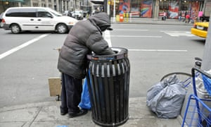 Homeless person searching through rubbish bin on New York city street