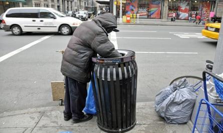 Homeless person searching through rubbish bin on New York city street
