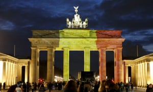 People stand in front of the Brandenburg gate, which is illuminated in black, yellow and red in the colours of the Belgian flag in tribute to victims of Tuesday's attacks in Brussels in Berlin.