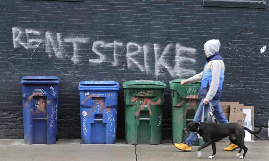 A pedestrian walks past graffiti that reads 'rent strike' in Seattle, Washington, on 1 April.