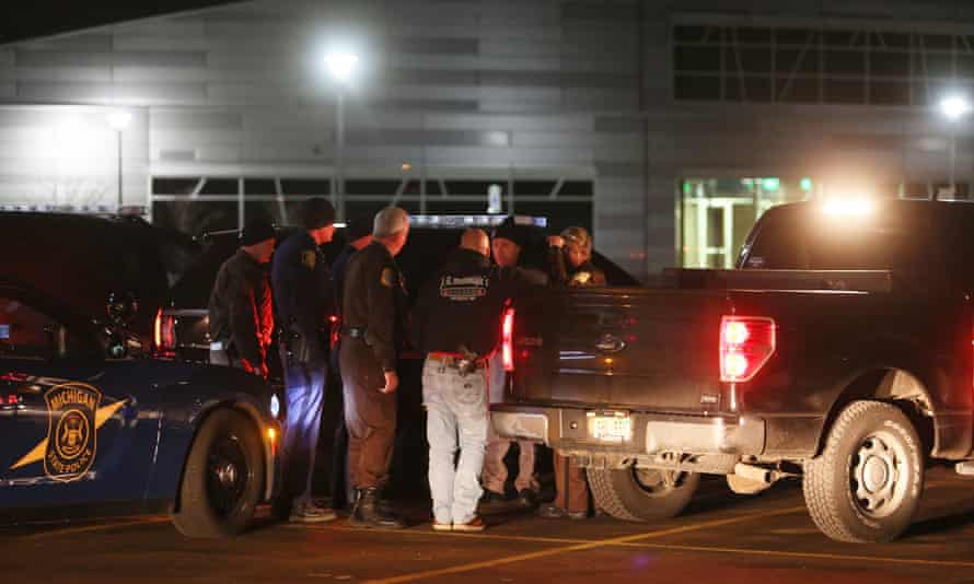 Police meet at Kalamazoo Valley community college during the manhunt.