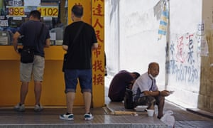 A man has lunch beside a money exchange store in Hong Kong.