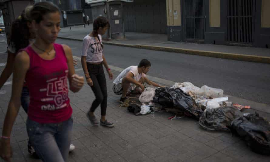 A man searches for food in the rubbish on a pavement in Caracas, Venezuela.
