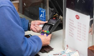 a man withdraws cash with a debit card at the Post Office counter
