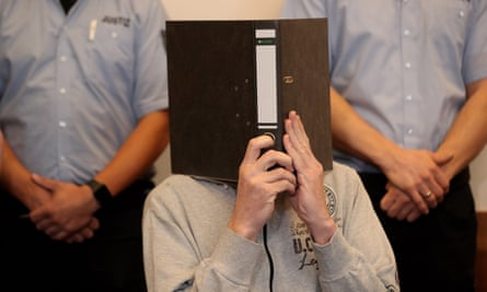 Andreas V covers his face at the district court in Detmold, Germany.