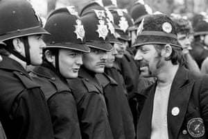 Picket wearing a joke police helmet talking to Police Officers without identification numbers at Orgeave, 6 June 1984