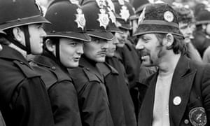 Miner wearing fake police helmet talks to officers at Orgreave