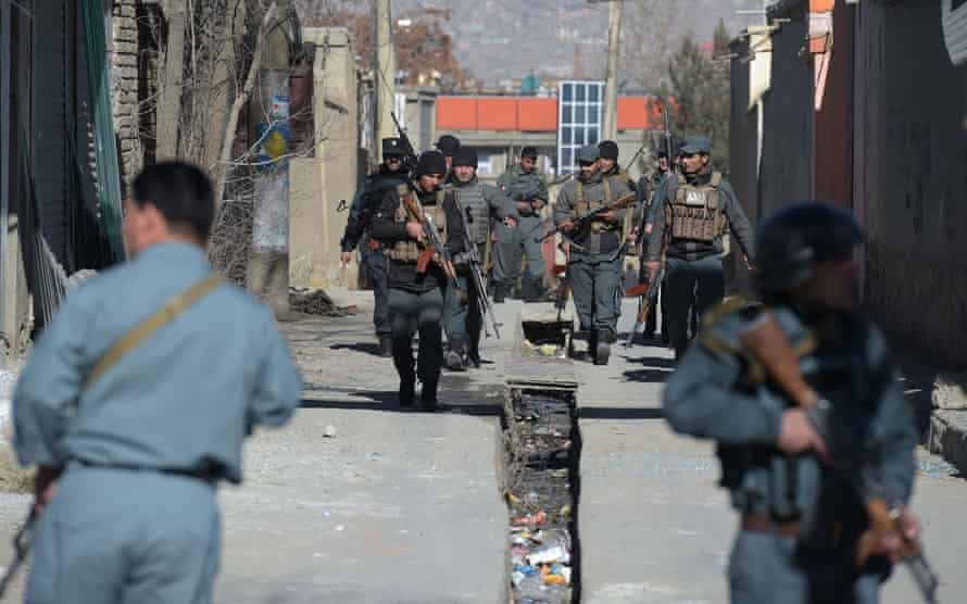 Police officers keep watch after the explosions in Kabul.