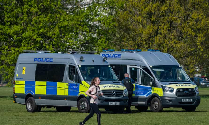 A jogger in front of two parked police vans in a London park.