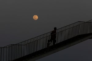 A man and child walk on a bridge with a rising pink supermoon in the background, as the outbreak of Covid-19 continues in Karachi, Pakistan.