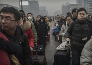 Travellers line up at Beijing railway station to present their tickets before boarding trains home
