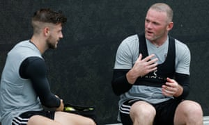 Wayne Rooney chats to new teammate Paul Arriola during a DC United training session