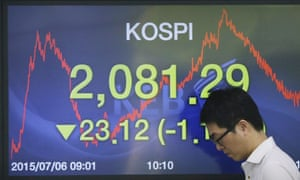 A currency trader walks by a screen showing the Korea composite stock price index at the Korea Exchange Bank headquarters in Seoul.