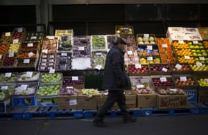 A customer walks past a display of produce at the Hunts Point Terminal Produce Market in the Bronx borough of New York, U.S.