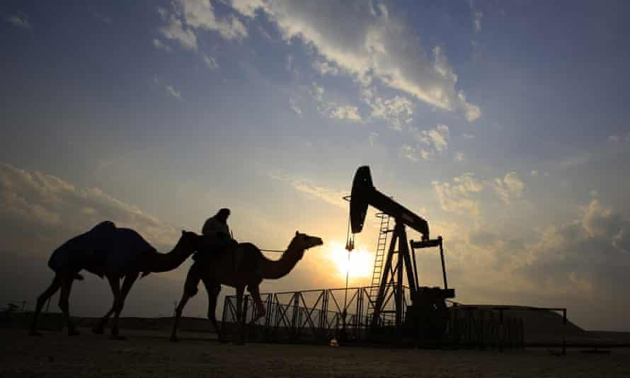 A man rides a camel through the desert oil field area of Sakhir, Bahrain