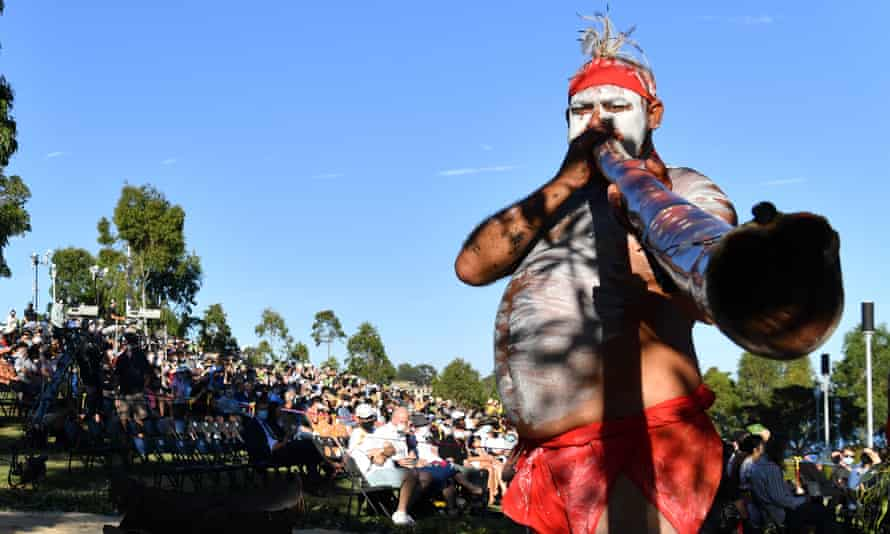 Indigenous performers play the didgeridoo during a smoking ceremony at Barangaroo Reserve during Australia Day in Sydney
