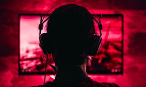 a woman wearing headphones plays a video game in a red-light saturated room