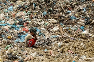 A young boy waits at a landfill site for his father who is collecting rubbish to resell in Lhokseumawe, Indonesia