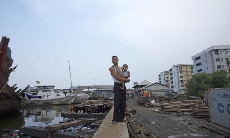 A man carries his baby along a seawall in an area lying more than a meter below sea level in the Maura Baru district in Jakarta, Indonesia. Jakarta, southeast Asia's largest city is sinking slowly into the sea.
