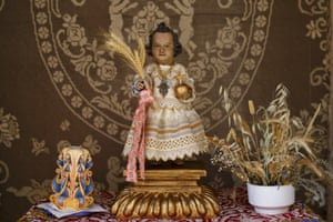 A carving of baby Jesus stands on an altar outside a house