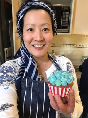 Katrina Lau Hammond poses in her kitchen with a matte blue cupcake.
