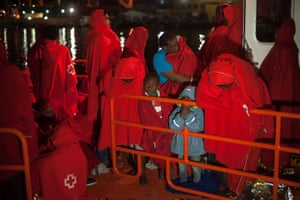 Málaga, Spain: Migrants wait to disembark from a boat after arriving at the port. Maritime officers rescued 81 people (including 14 children) on a dinghy crossing the western Mediterranean.