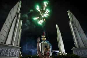 A protester flashes a three-finger salute as fireworks explode over the Democracy Monument