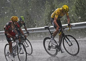 Chris Froome, in the yellow jersey, Richie Porte and Nairo Quintana climb in pouring rain and hail towards Andorra Arcalis during the ninth stage of the Tour de France