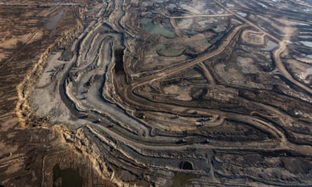 Trucks and machinery work a tar sands site in northern Alberta, Canada.
