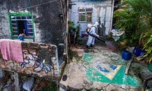 Man in protective gear sprays houses