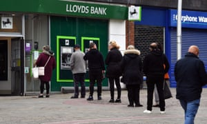 People adhere to social-distancing guidelines as they queue to enter a Lloyds bank in Barrow-in-Furness in May
