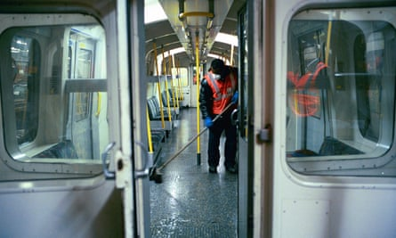 A cleaner sweeping the floor of a tube train.