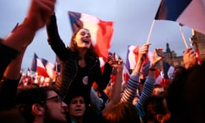 Supporters celebrate at a rally for Emmanuel Macron outside the Louvre on Sunday in Paris